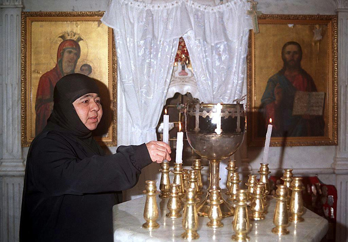 A Syrian nun lights candles inside the historical church of Mar Taqla in the village of Maaloula north of Damascus (AFP Photo)