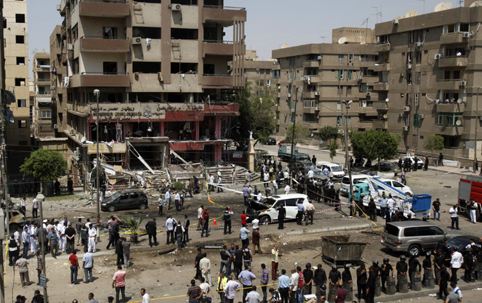 A general view shows policemen investigating next to burnt cars at the site of a bomb attack and assassination attempt near the house of Egypt's Interior Minister Mohamed Ibrahim in the Nasr City district of Cairo September 5, 2013. (Reuters/Amr Abdallah Dalsh)