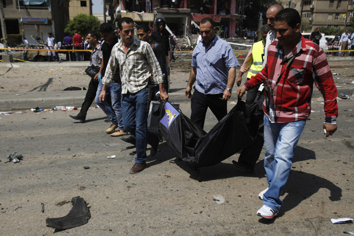Medics and police carry recovered body parts from the site of a bomb attack and assassination attempt near the house of Egypt's Interior Minister Mohamed Ibrahim in the Nasr City district of Cairo September 5, 2013. (Reuters/Amr Abdallah Dalsh)