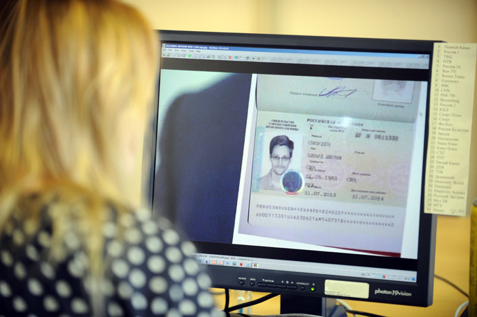 A woman watches a footage on her computer, showing the lawyer of fugitive US intelligence leaker Edward Snowden showing his client's one year's asylum permit at Sheremetyevo airport in Moscow on August 1, 2013. (AFP Photo)
