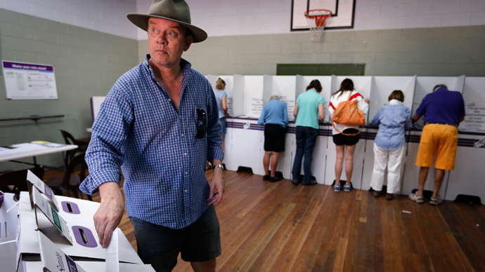 A man wearing an Australian bush hat casts his vote at a polling booth located in a small hall in Sydney September 7, 2013 (Reuters / David Gray)