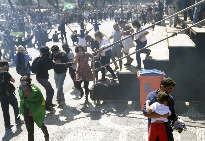 A man walks away with his son as demonstrators clash with riot police near an audience area during a protest as they try to approach a military parade on Brazil's Independence Day in Rio de Janeiro September 7, 2013. (Reuters/Ricardo Moraes)