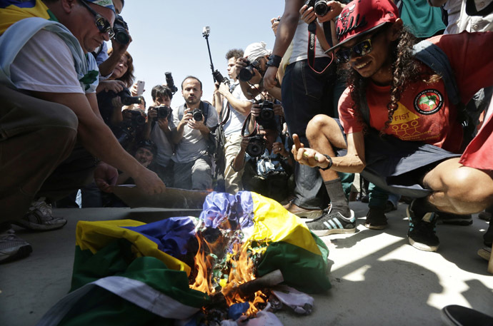 Demonstrators burn a Brazilian flag during a protest on Brazil's Independence Day in Rio de Janeiro September 7, 2013. (Reuters/Ricardo Moraes)