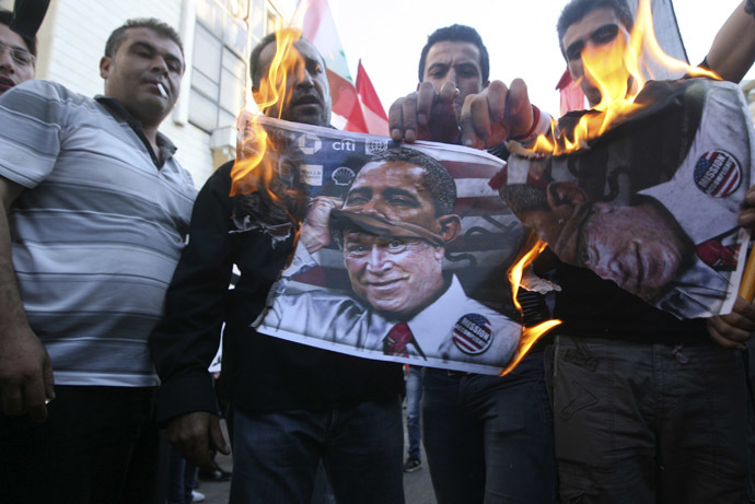 Activists burn a poster depicting former U.S President George Bush disguised as current U.S President Barack Obama during a protest against potential U.S. strikes on Syria, near the U.S. embassy in Awkar, north of Beirut, September 7, 2013. (Reuters/Hasan Shaaban)