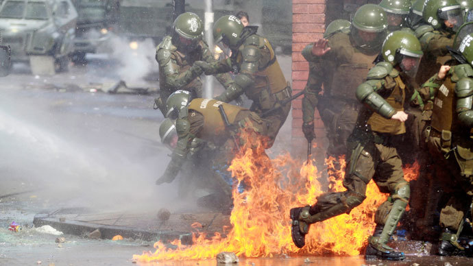 A riot policeman (L) is helped by fellow policemen after catching fire from a molotov cocktail bomb during a protest marking the 1973 military coup in Santiago, September 8, 2013.(Reuters / Ivan Alvarado)