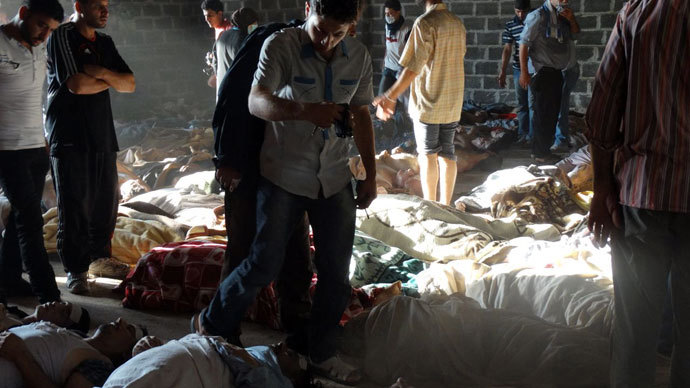 Syrian opposition's Shaam News Network shows people inspecting bodies of children and adults laying on the ground as Syrian rebels claim they were killed in a toxic gas attack by pro-government forces in eastern Ghouta, on the outskirts of Damascus on August 21, 2013.(AFP Photo / Shaam News Network)