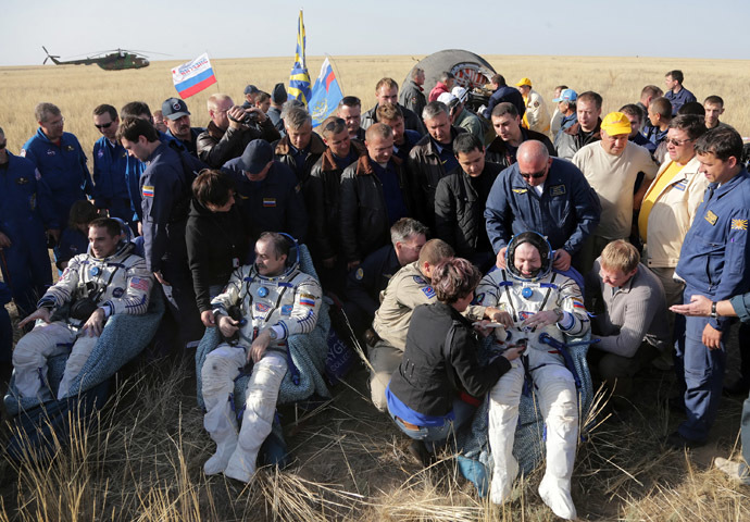 US astronaut Chris Cassidy (L) together with Russian cosmonauts Pavel Vinogradov (C) and Alexander Misurkin (R) rest shortly after their landing on board the Soyuz TMA-08M space capsule some 146 km southeast of the town of Zhezkazgan in Kazakhstan,, on September 11, 2013. (AFP Photo/Maxim Shipenlov)