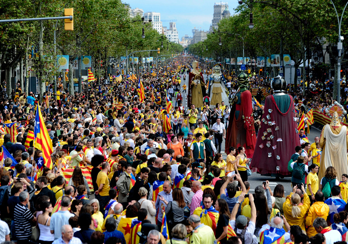Giants walk past Catalans gathering in a bid to create a 400-kilometre (250-mile) human chain, part of a campaign for independence from Spain during Catalonia National Day, or Diada, on Passeig de Gracia in Barcelona, on September 11, 2013 (AFP Photo / Josep Lago)