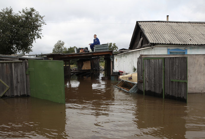 A woman sits on the roof of her flooded dwelling outside Komosomolsk-on-Amur in Russia's far eastern Khabarovsk region, September 7, 2013. (Reuters/Vladimir Barsukov)