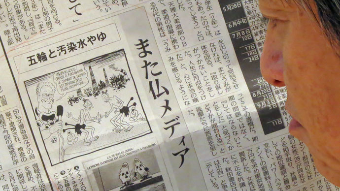 A man reads a Japanese local newspaper reporting cartoons published in a French newspaper, in Tokyo on September 12, 2013..(AFP Photo / Kazuhiro Nogi)
