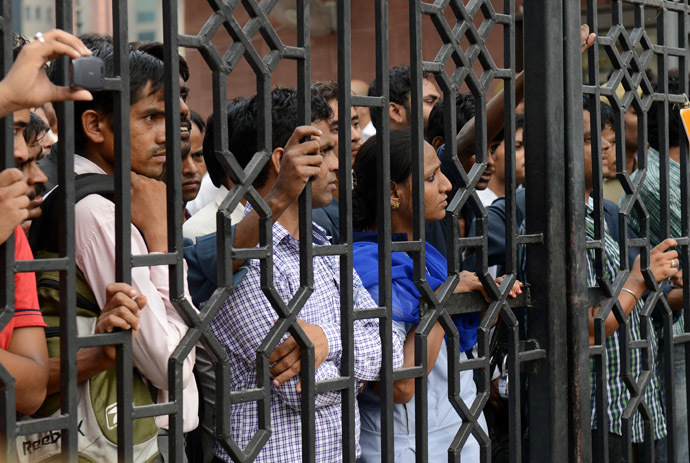 An Indian woman stands among a group of men inside the gate of the Saket district court in New Delhi on September 13, 2013, as they watch members of the media interview a lawyer for one of the convicted men in a rape case. (AFP Photo/Roberto Schmidt)