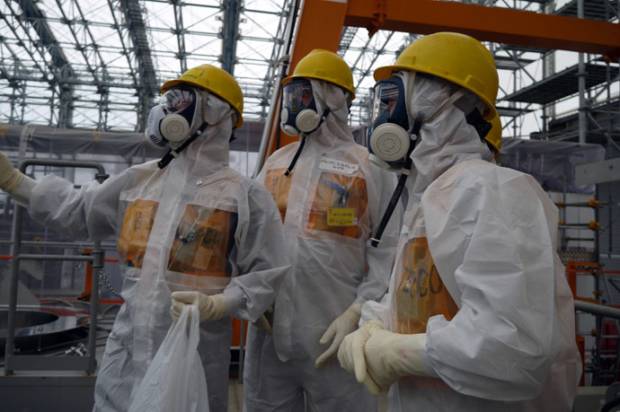 This handout picture taken by Tokyo Electric Power Co (TEPCO) on September 12, 2013 shows Luke Barret (C), external professional for TEPCO's contaminated water and tank countermeasures headquarters, inspecting TEPCO's Fukushima Dai-ichi nuclear power plant at Okuma town in Fukushima prefecture. (AFP/TEPCO)