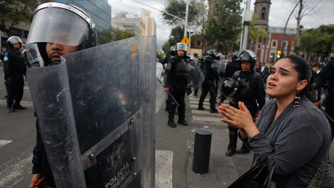 A woman pleads for no more violence to a riot federal police officer after striking members of the teachers' union CNTE were evicted from Zocalo Square in downtown Mexico City September 13, 2013.(Reuters / Tomas Bravo)
