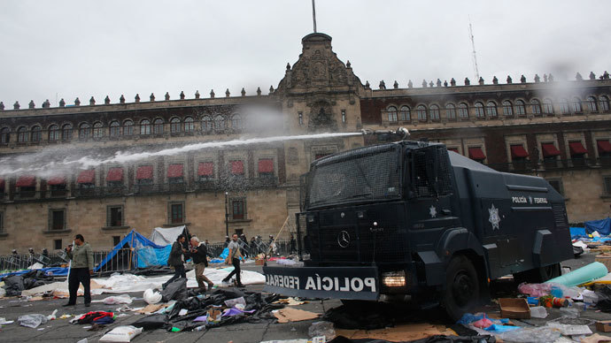 A federal police riot truck sprays water after striking members of the teachers' union CNTE are evicted from Zocalo Square in downtown Mexico City September 13, 2013.(Reuters / Tomas Bravo)