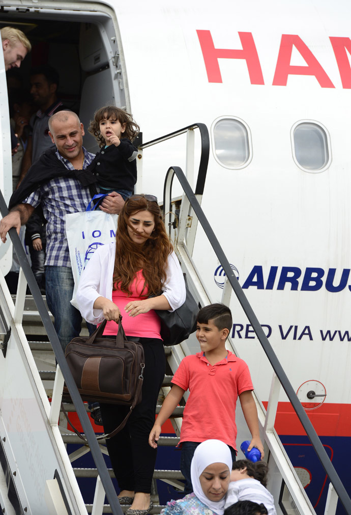 Syrian refugees disembark from a plane in Hanover on September 11, 2013. (AFP Photo/John Macdougall)