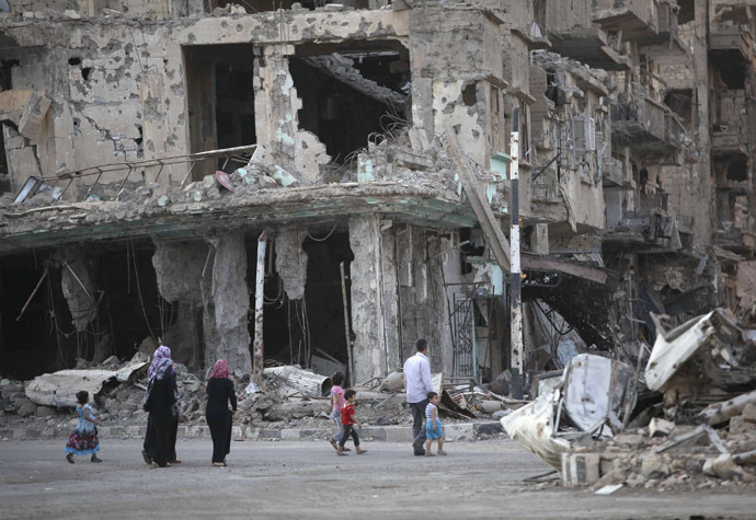 People walk along a damaged street filled with debris in Deir al-Zor September 4, 2013. (Reuters//Khalil Ashawi)