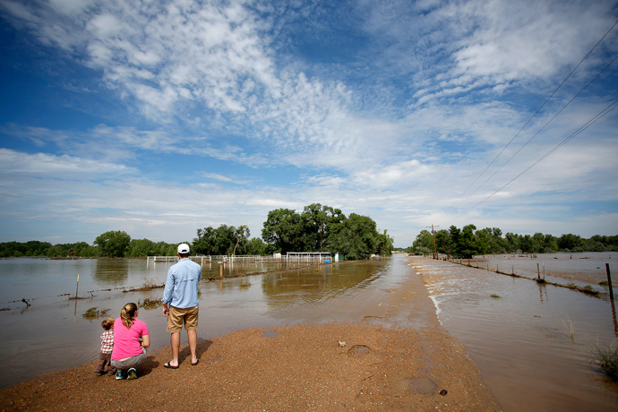 Allison Wold of Denver, Colorado and her nephew, Jack Wold, take in a flooded ranch home with John Brinckerhoff, also of Denver after heavy flooding September 14, 2013 near Dearfield, Colorado (AFP Photo / Marc Piscotty)