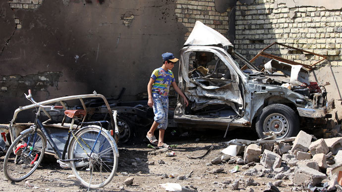 An Iraqi child stands by the wreckage of a burnt car on the site of a car bomb explosion in the city of Suweirah, south of Baghdad, on September 15, 2013.(AFP Photo / Ahmad Al-Rubaye)