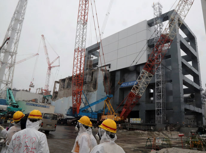 Reporters and Tokyo Electric Power Co workers look up the unit 4 reactor building during a media tour at TEPCO's Fukushima Dai-ichi nuclear plant in the town of Okuma, Fukushima prefecture in Japan on June 12, 2013.(AFP Photo / Noboru Hashimoto)