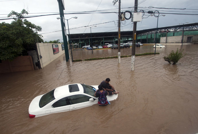 Two men wait for help in a flooded street in Acapulco, Guerrero state, Mexico, after heavy rains hit the area on September 16, 2013. (AFP Photo/Pedro Pardo)