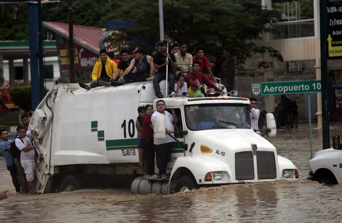 Residents attempt to leave the flooded area in Acapulco, Guerrero state, Mexico, after heavy rains hit the area on September 16, 2013. (AFP Photo/Pedro Pardo)