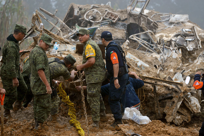 Mexican soldiers and police look for victims of a landslide caused by heavy rains in Xaltepec community, State of Veracruz, Mexico on September 16, 2013. (AFP Photo)