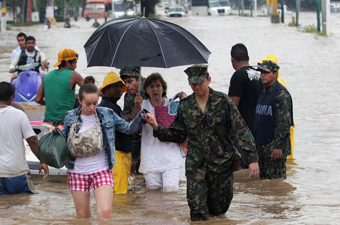 Tourists wade through a flooded street in Acapulco, Guerrero state, Mexico, after heavy rains hit the area on September 16, 2013 (AFP Photo)