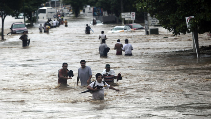 Residents attempt to flee from the flooded area in Acapulco, Guerrero state, Mexico, after heavy rains hit the area on September 16, 2013. (AFP Photo/Pedro Pardo)