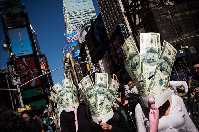 Occupy Wall Street protesters wearing masks made out of enlarged dollar bills act in a short skit in Times Square on September 17, 2013 in New York City. (AFP Photo / Andrew Burton)