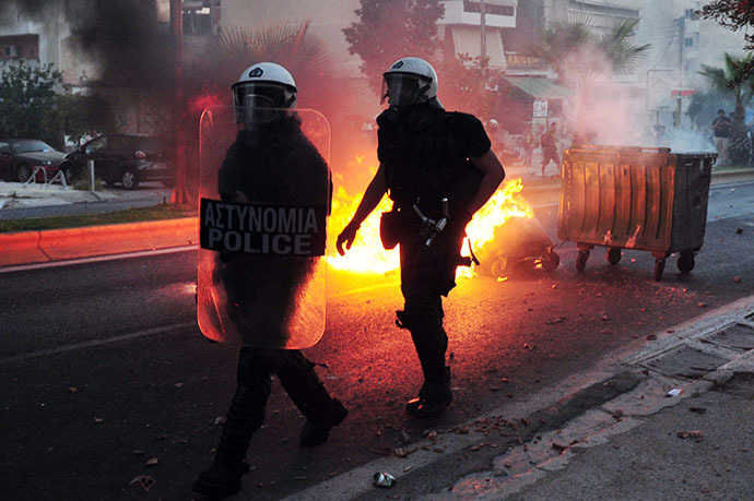 Police advance past a burning barricade as they clash with anti-fascist protesters in the western Athens working class suburb of Keratsini on September 18, 2013, after a leftist musician was murdered by a suspected neo-Nazi. (AFP Photo / Louisa Gouliamaki)