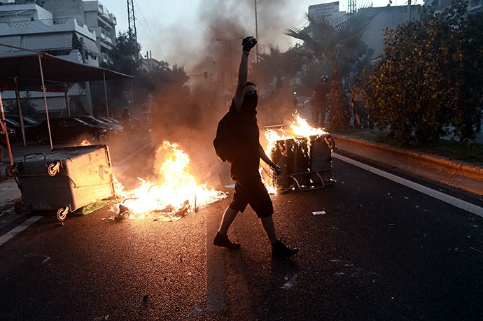 A protestor raises his fist as anti-fascist demonstrators clash with riot police in Athens on September 18, 2013, after a leftist musician was murdered by a suspected neo-Nazi. (AFP Photo / Aris Messinis)