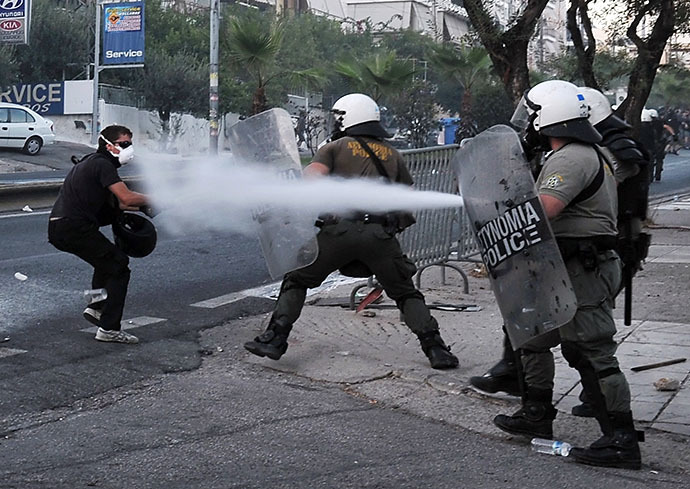 Police spray a protester with tear gas during clashes with anti-fascist demonstrators in the western Athens working class suburb of Keratsini on September 18, 2013, after a leftist musician was murdered by a suspected neo-Nazi. (AFP Photo / Louisa Gouliamaki)