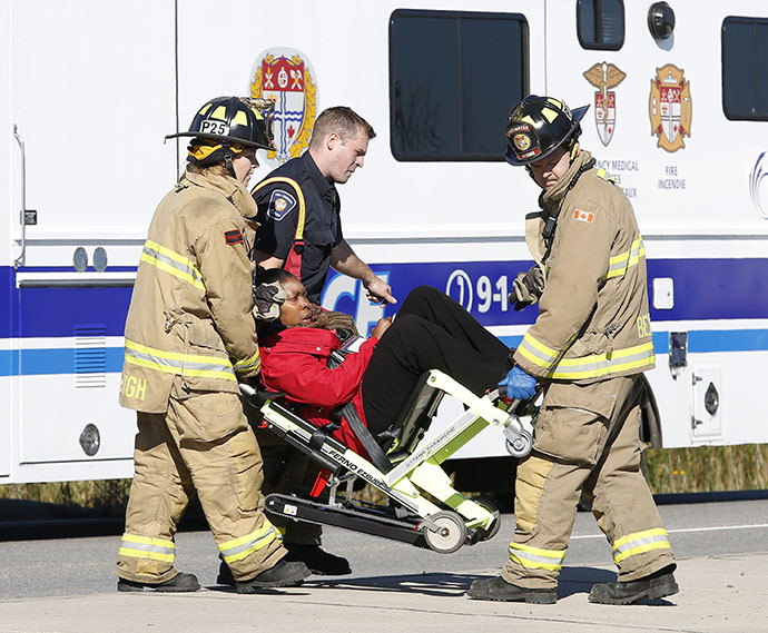 Emergency workers take a person away at the scene of an accident involving a bus and a train in Ottawa September 18, 2013. (Reuters / Chris Wattie)