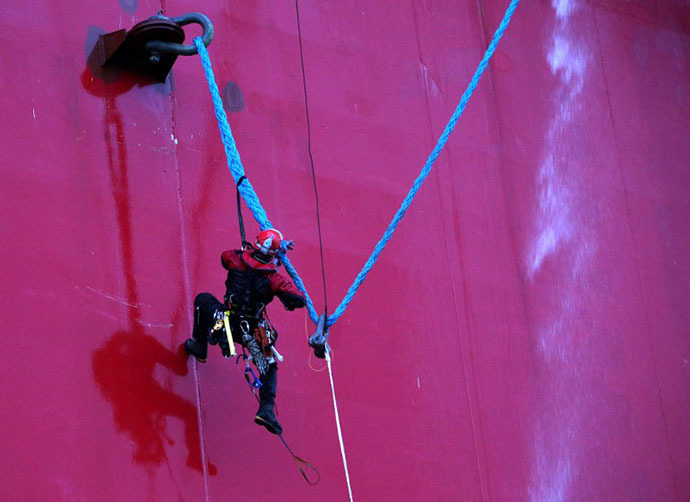 A handout photo taken by Greenpeace on September 18, 2013, shows a Greenpeace activist attempting to climb Gazprom's 'Prirazlomnaya' Arctic oil platform somewhere off Russia north-eastern coast in the Pechora Sea. (AFP Photo / Greenpeace / Denis Sinyakov)