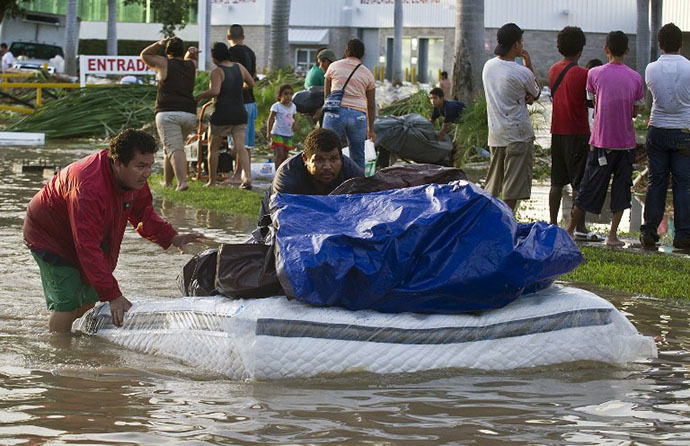 Looters flee with goods from a supermarket in Acapulco, state of Guerrero, Mexico, on September 17, 2013 as heavy rains hit the country. (AFP Photo / Ronaldo Schemidt)