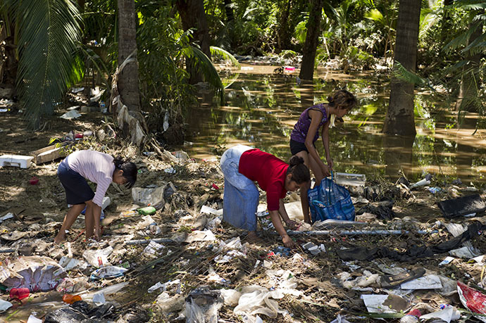 Residents search for food amid the debris in a flooded street of Acapulco, state of Guerrero, Mexico, on September 18, 2013 as heavy rains hit the country. (AFP Photo / Ronaldo Schemidt)