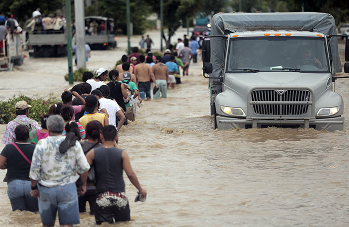 Residents and tourists wade through a flooded street in Acapulco, Guerrero state, Mexico, on September 17, 2013 as heavy rains hit the country. (AFP Photo / Pedro Pardo)