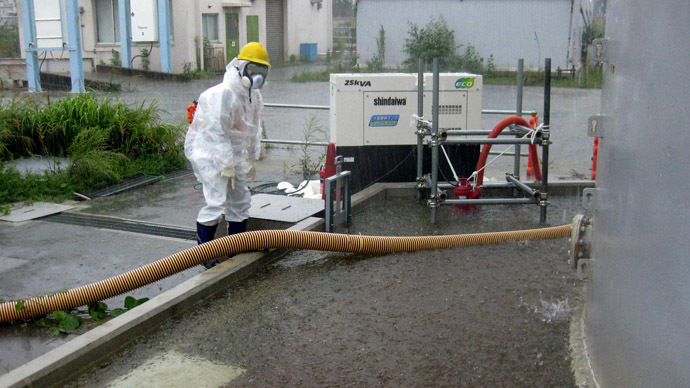 This handout picture taken by Tokyo Electric Power Co. (TEPCO) on September 15, 2013 and released on September 17 shows a TEPCO worker pumping rainwater around the contamination water tank at TEPCO's Fukushima dai-ichi nuclear plant at Okuma town in Fukushima prefecture. (AFP Photo/TEPCO)