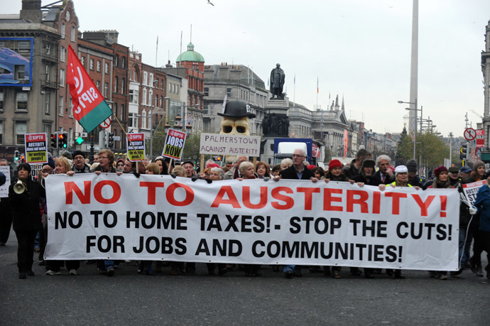 Protestors display placards and banners as they march against Government austerity measures in Dublin, Ireland on November 24, 2012. (AFP Photo/ Barry Cronin)