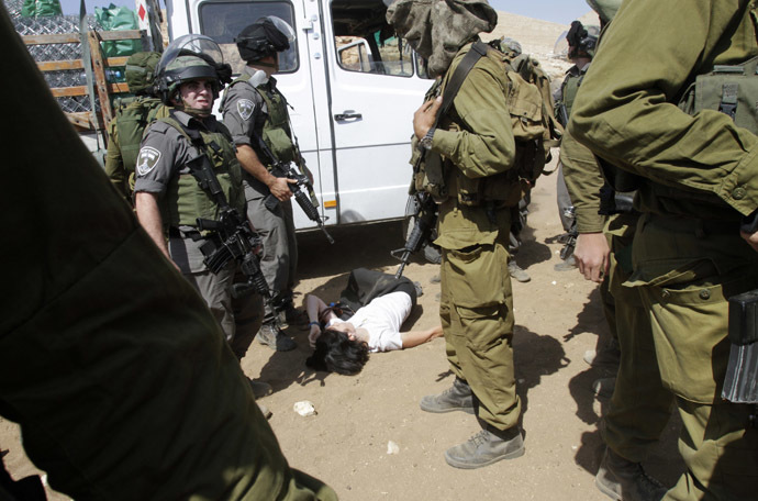 French diplomat Marion Castaing lays on the ground after Israeli soldiers carried her out of her truck containing emergency aid, in the West Bank herding community of Khirbet al-Makhul, in the Jordan Valley September 20, 2013. (Reuters/Abed Omar Qusini)