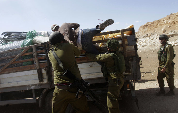 sraeli soldiers pull a Palestinian off a truck loaded with items European diplomats wanted to deliver to locals in the West Bank herding community of Khirbet al-Makhul, in the Jordan Valley September 20, 2013. (Reuters/Abed Omar Qusini)