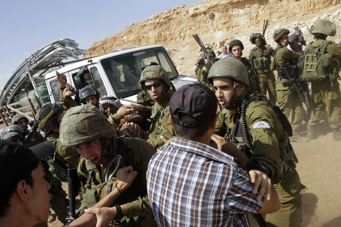 Israeli soldiers scuffle with Palestinians near a truck loaded with items European diplomats wanted to deliver to locals in the West Bank herding community of Khirbet al-Makhul, in the Jordan Valley September 20, 2013. (Reuters/Abed Omar Qusini)
