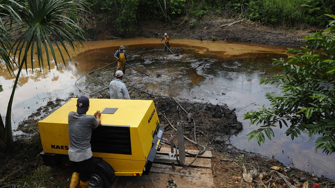 Employees of state-owned Petroecuador work on environmental cleansing operations of a 30-year old oil spillage at the Rumipamba commune, 200 mt from the Auca Sur 1 oil well --operated by US Chevron Texaco in the seventies--, in the province of Orellana, Amazonia, on February 20, 2011.(AFP Photo / Rodrigo Bгутdia)