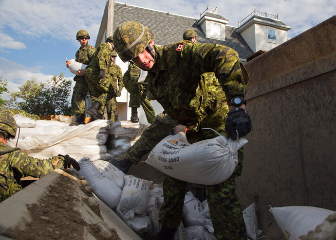 Canadian Armed Forces soldiers from the The Calgary Highlanders start to sandbag from the rising Bow River in the community of Ingelwood in Calgary, Alberta June 22, 2013.(Reuters / Melissa Renwick)