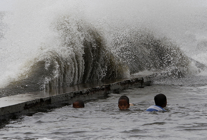 Children swim in a flooded walkway as rough waves crash on concrete banks along the coast of Manila Bay brought by Super Typhoon Usagi in Navotas City, metro Manila September 21, 2013. (Reuters / Romeo Ranoco)