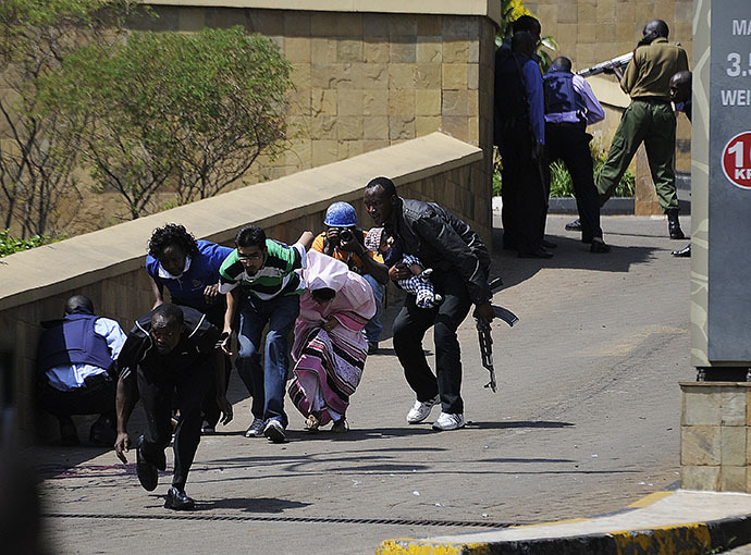 A policeman carry's a baby to safety after masked gunmen stormed an upmarket mall and sprayed gunfire on shoppers and staff, killing at least fifty nine on September 21, 2013 in Nairobi. (AFP Photo / Simon Maina)