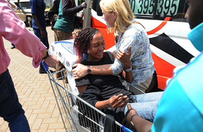 A woman is trolled into an ambulance after masked gunmen stormed an upmarket mall and sprayed gunfire on shoppers and staff, killing at least fifty nine on September 21, 2013 in Nairobi. (AFP Photo / Simon Maina)