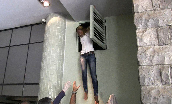 An image grab taken from AFP TV shows a Kenyan woman coming out of an air vent where she was hiding during an attack by masked gunmen at a shopping mall in Nairobi on September 21, 2013 (AFP Photo / AFPTV)