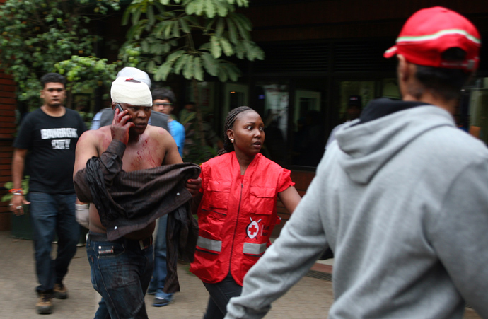 An injured Kenyan man talks on the phone upon his arrival at the Aga Khan Hospital in Nairobi, on September 21,2013 after masked attackers stormed a packed upmarket shopping mall, spraying gunfire and killing 59 people and wounding dozens more before holing themselves up in the complex (AFP Photo / Hoss Njuguna)