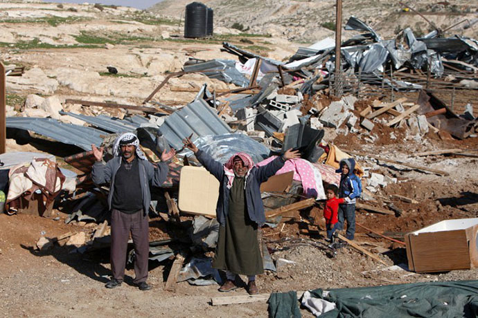 (FILE photo) Palestinian Bedouin men react amidst the rubble of a structure after it was razed by the Israeli army in the West Bank village of Zayem, near Jerusalem (AFP Photo / Ahmad Gharabli)
